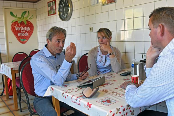Adviseur Roland van Rooij, van het Centrum voor Criminaliteitspreventie en Veiligheid, overlegt aan de keukentafel van de Dongense aardbeientelers Jeroen en Nancy Peeters.
