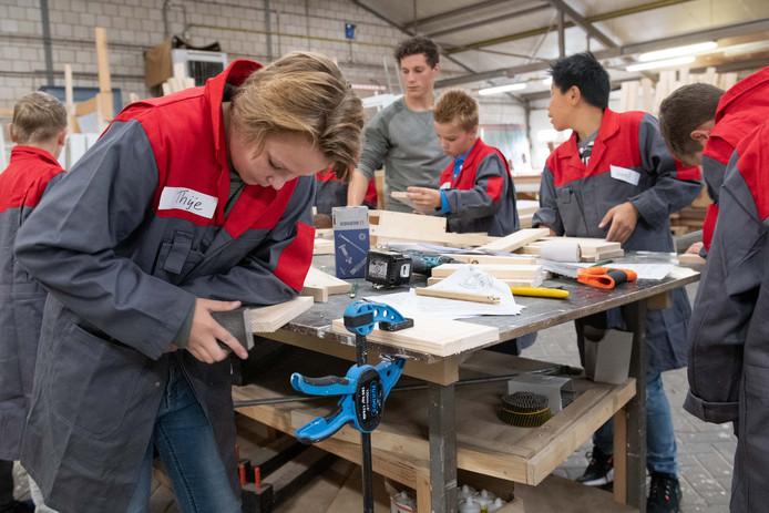 Leerlingen uit de Klusklas van basisschool De Wiekslag druk bezig bij Aannemersbedrijf Hoek uit Tubbergen.