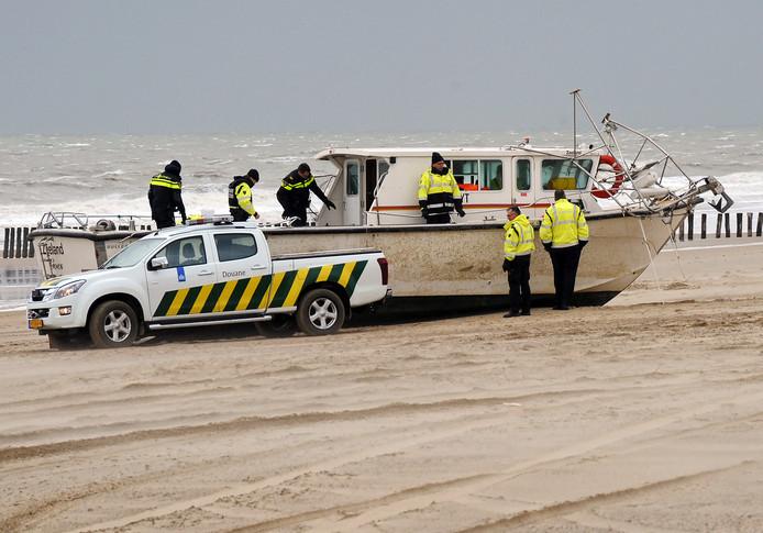 Douanepersoneel onderzoekt het aangespoelde sportvisbootje.