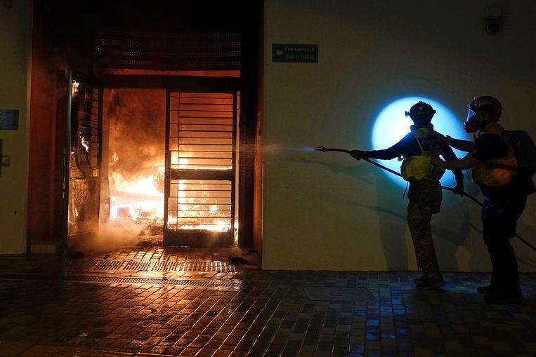 Brandweermannen blussen de brand in de lobby.