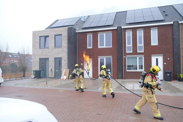 De vlammen sloegen uit de voordeur van de woning.