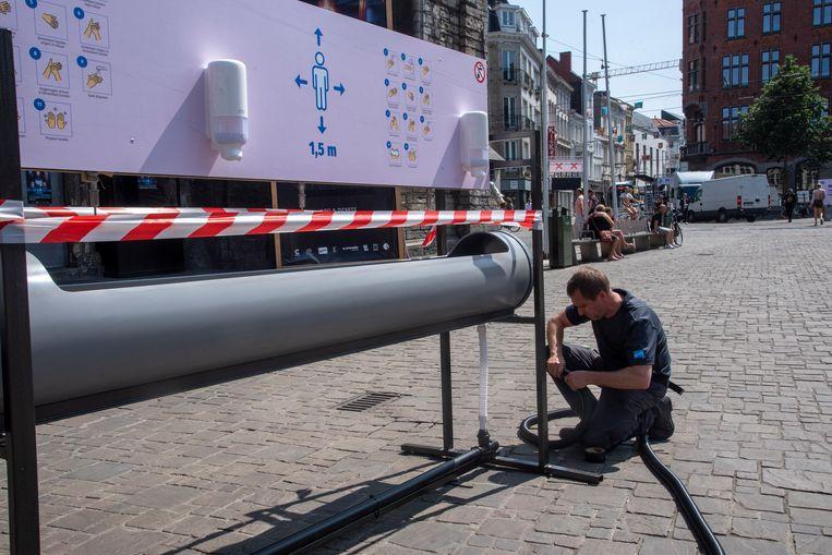 Medewerkers van de stad sluiten de openbare wasbakken aan op het waternet.