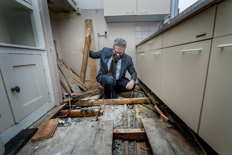 Chris Pettersson,  regiomanager bij Ymere, bekijkt een loden leiding in een huurwoning  in Noord. Beeld Jean-Pierre Jans
