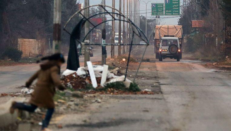 Een meisje in Madaya steekt de straat over nadat een hulpkonvooi is langsgereden. Beeld afp