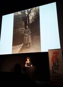 Dieuwertje Blok tijdens voordracht met achter haar een foto van haar Joodse moeder toen zij zeventien jaar was.