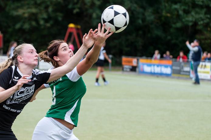 Tjoba-korfbalster Esmee Walraven (rechts) probeert in een uiterste krachtsinspanning bij de bal te komen.