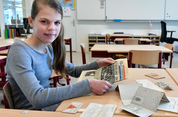 Nienke heeft nog oude persoonsbewijzen en stoffen kledingnummers van haar overgrootvader meegenomen. In haar hand een krant van 10 mei 1945.