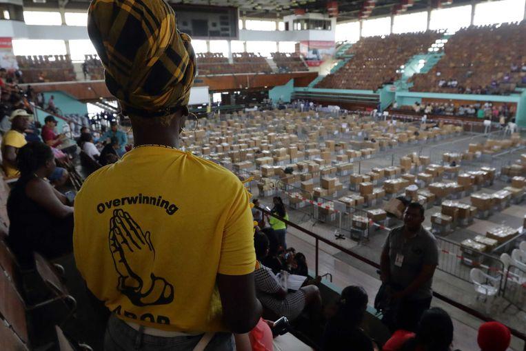 Leden van politieke partijen houden toezicht in de Anthony Nesty Sporthal, waar autoriteiten de laatste check-up doen van de processen-verbaal van de 274 stembureaus. De verkiezingen in Suriname verliepen behoorlijk chaotisch.  Beeld ANP