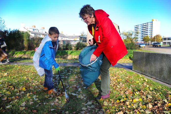 Mauro (7) van groep 4 van de Louise de Colignyschool helpt wethouder Els Verhage met het verzamelen van kleine stukjes plastic afval in Paauwenburg.