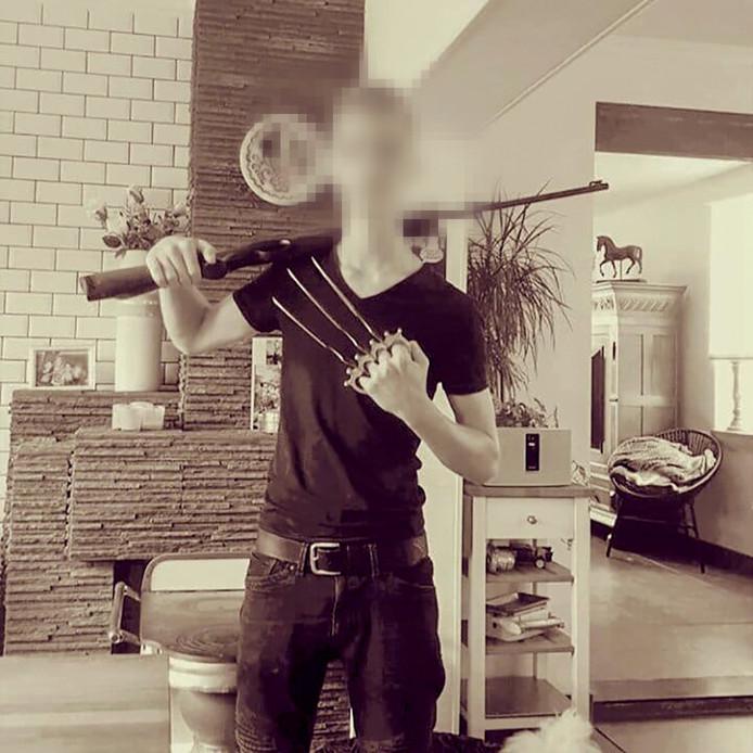 De 16-jarige schutter poseert met wapens.