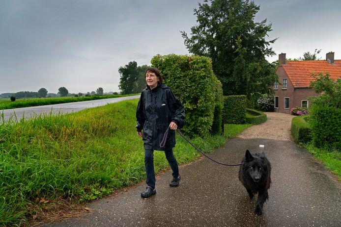 Hanneke Herders op de dijk met haar hond Kiko. Zij maakt zich grote zorgen over de komst van zo veel windmolens zo dicht bij haar huis.
