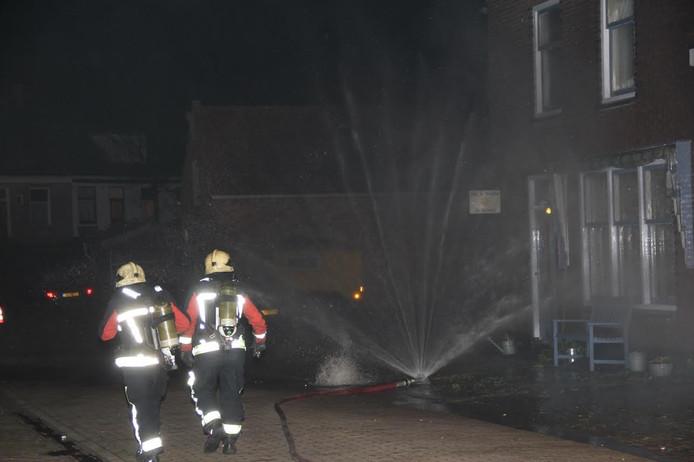 Gas borrelt omhoog in de straat met daarnaast het waterscherm van de brandweer.