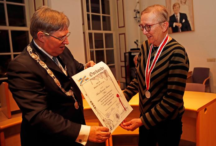 Burgemeester Rensen geeft Mia Ariaans de oorkonde die hoort bij de eretitel van Poorteres van het jaar.