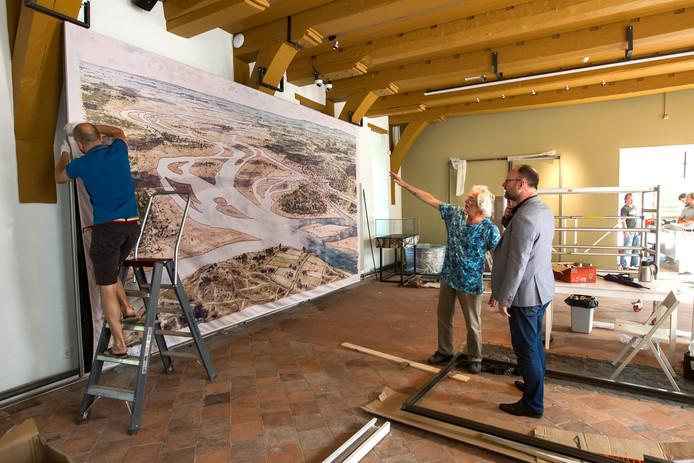 De IJssel anno 750 na Chr.  De tekening van Peter Paul Hattinga Verschure krijgt -sterk uitvergroot- een plaats in de nieuwe Waag. Directeur Garrelt Verhoeven van Deventer Verhaal luistert naar de uitleg van de stadstekenaar, terwijl Timo Bralts van Bestwerk het doek bevestigt.