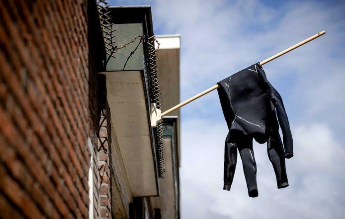 Een wetsuit hangt halfstok in Scheveningen.
