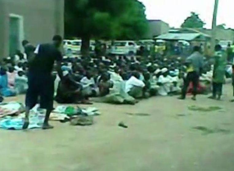 Een beeld uit een video van Amnesty waarop volgens de organisatie te zien is hoe Nigeriaanse militairen Boko Haram-leden één voor één de keel doorsnijden Beeld Amnesty