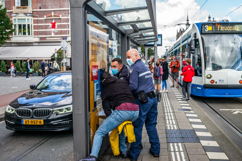 Een man wordt opgepakt door handhavers, vermoedelijk vanwege het niet (willen) dragen van een mondkapje in de tram. Beeld Joris Van Gennip