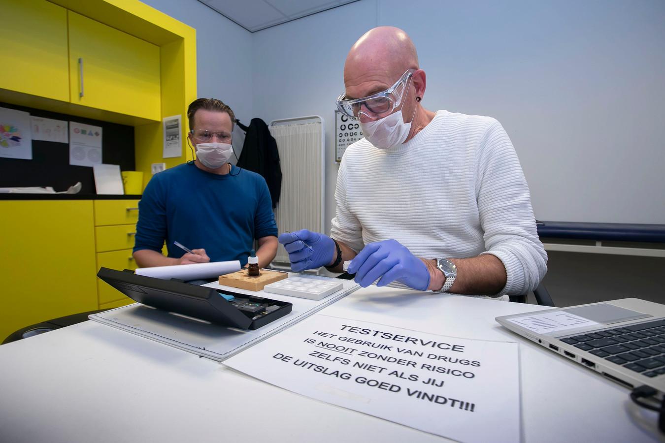Charles Dorpmans (rechts) van Novadic Kentron in Brabant neemt een monster van een te testen designerdrug. Veiligheidsbril, masker en handschoenen zijn tegenwoordig verplicht.