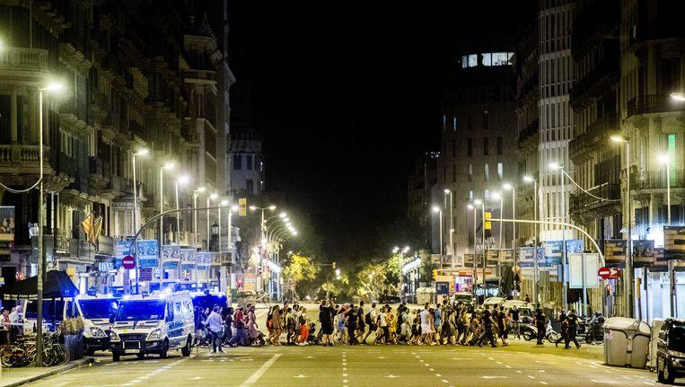 Toeristen worden begeleid door de politie over de afgezette Ramblas, donderdagnacht. Beeld anp