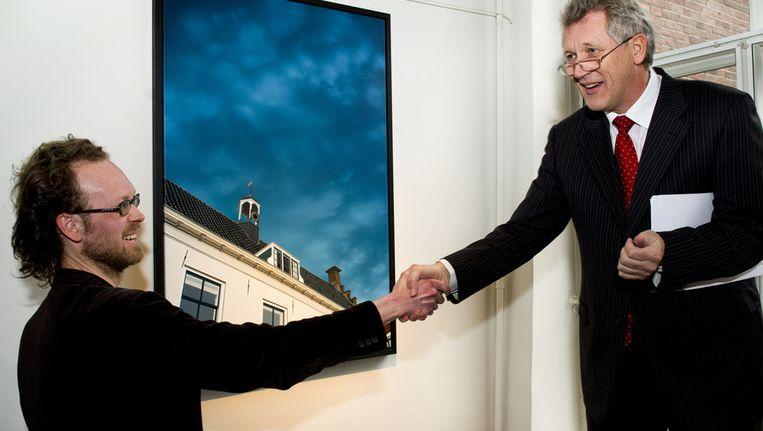 Dirk Scheringa (rechts) onthult een schilderij van Dennis Teunissen. Beeld ANP