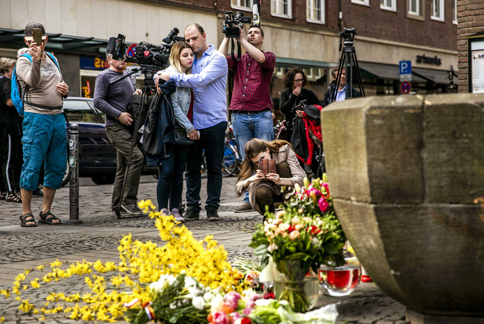 Mensen bekijken de plek in het centrum van Münster, waar een dag eerder een busje inreed op een vol terras