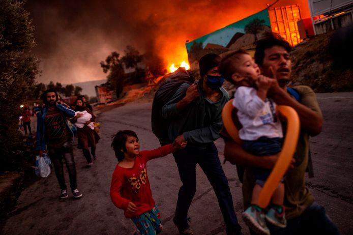 Een migrantenfamilie vlucht voor het vuur in opvangkamp Moria begin deze maand op het Griekse eiland Lesbos.