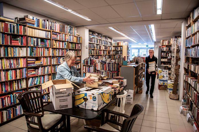 José van Lieshout en medewerker Ton moeten zo'n 50.000 boeken verplaatsen voordat de tweedehandsboekenwinkel Het Boekenschop weer open kan.