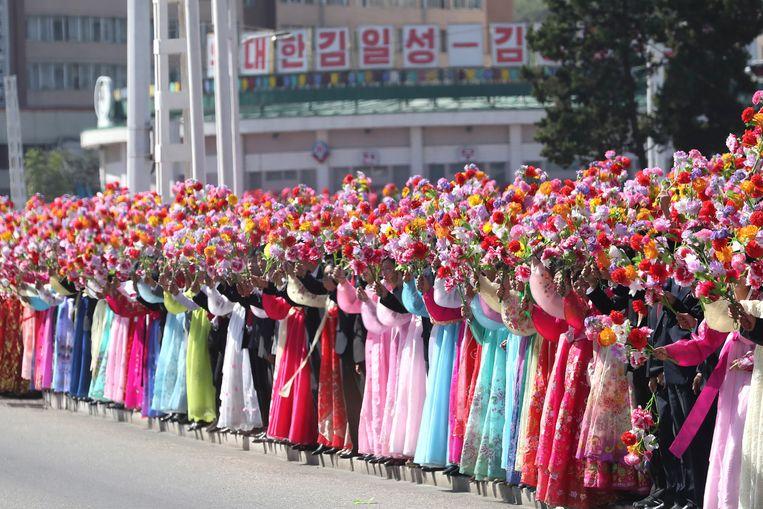 Vrouwen in traditioneel kostuum verwelkomen de Koreaanse leiders. Beeld AP