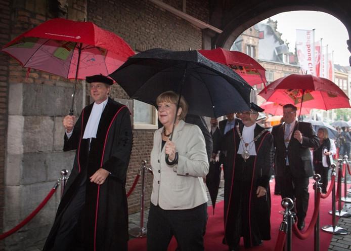 Angela Merkel arriveert in de stromende regen bij de Stevenskerk in Nijmegen.