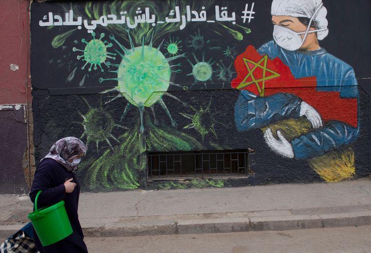 In Sale, Marokko, loopt een vrouw langs een muurschildering waarop wordt gewaarschuwd voor het covid-19-virus. Beeld Jalal morchidi / EPA
