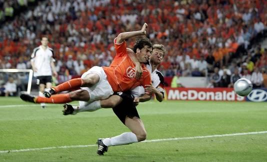 Ruud van Nistelrooy wordt vastgehouden door Christian Worns tijdens Duitsland Nederland in 2004 in Porto, maar de Nederlander scoort wel. © ANP