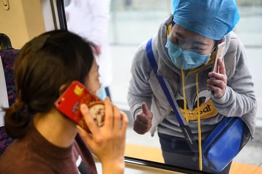Een verpleegster praat met iemand in een trein via haar mobiele telefoon.