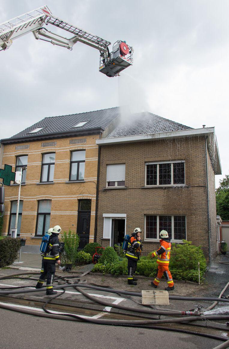 De brandweer blust het dak van de woning in de Weverstraat. Op de zolder werd een cannabisplantage aangetroffen.