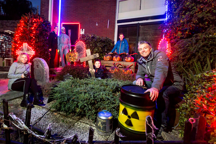 Marco Beuman met zijn familie voor zijn huis dat dagelijks spookachtiger wordt.