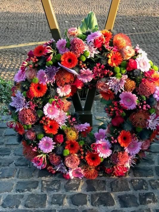 De bloemen bij het herdenkingsmonument.