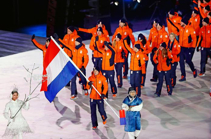 Jan Smeekens draagt de Nederlandse vlag bij de openingsceremonie