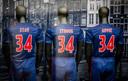 In de etalage van de fanshop van Ajax staan drie clubshirts die samen de tekst Stay Strong Appie laten zien. De shirts zijn voorzien van rugnummer 34, het nummer van Abdelhak Nouri