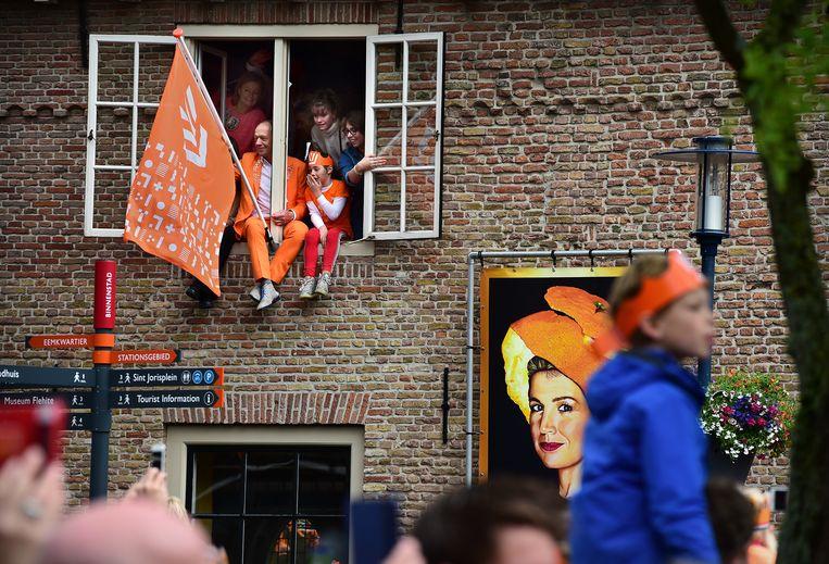 Mensen zitten in het raamkozijn tijdens het bezoek van koning Willem-Alexander met zijn familie aan Amersfoort. Beeld Marcel van den Bergh