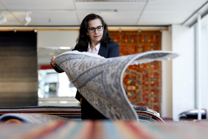 Mevrouw Andacheh slaat de tapijten open, zoals je een metersgrote pagina zou omslaan.