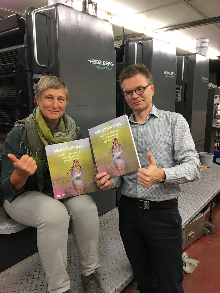 Conservator Kristine Van De Velde en ondervoorzitter en bezieler van het boek, krijgen het eerste exemplaar overhandigd.