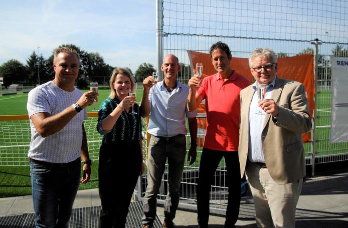 Het glas wordt geheven op het nieuwe kunstgrasveld door (vlnr) Paul Leertouwer (CHRC), wethouder Marinka Mulder, Richard Veldt (RVW), Koen Beenen (Redichem) en Jos Buijs (Doelum).