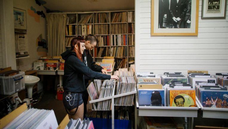 Klanten in Record Palace. Aan de wand een foto van The Small Faces Beeld Tammy van Nerum