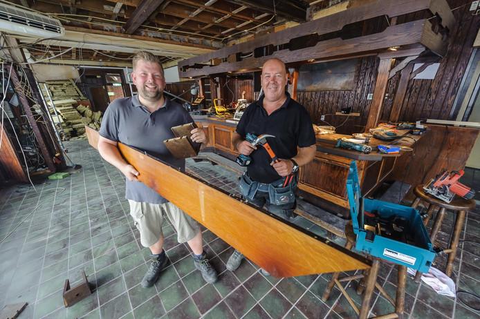 Tom Keizer (links) en Fred van Regteren zijn bezig met het strippen van de bruine inrichting van café Peca.