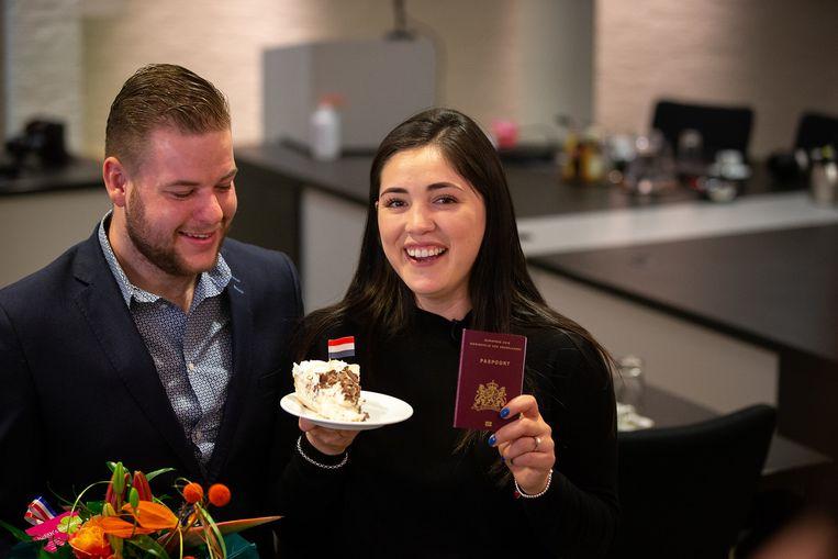 Gabriela Bayardo, naast vriend Mike Schoessler, toont haar Nederlandse paspoort. Beeld
