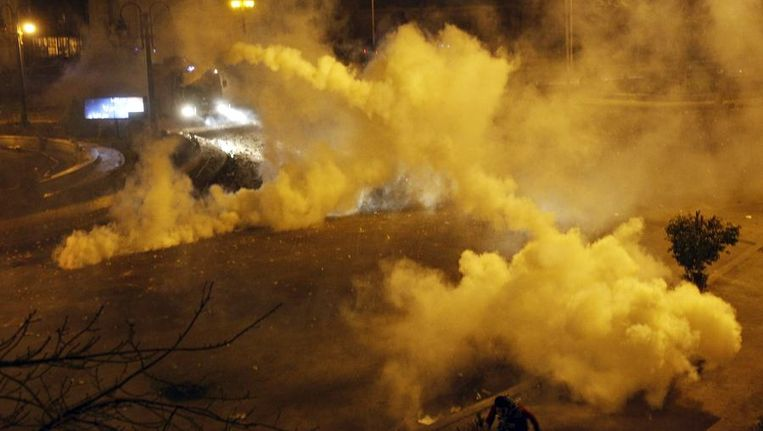 Veiligheidstroepen schieten met traangas bij een confontatie met demonstranten voor het presidentiële paleis. Beeld reuters