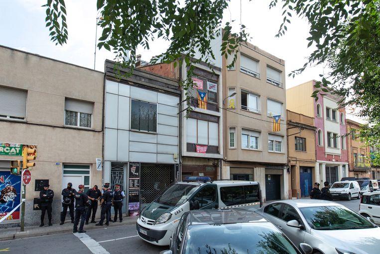 Leden van de Spaanse politie staan bij een huis waar een inval is gedaan. Beeld EPA