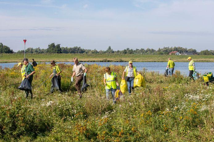 Vrijwilligers van ZAAP verzamelen afval in de uiterwaarden van de Palmerswaard.