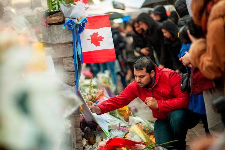 Een man schrijft een boodschap voor de slachtoffers van de aanval in Toronto.  Beeld AFP