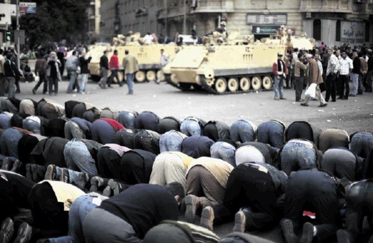 Een Egyptische familie probeert even op adem te komen tijdens de massaprotesten gisteren tegen het bewind van Hosni Moebarak. (FOTO AP) Beeld AP