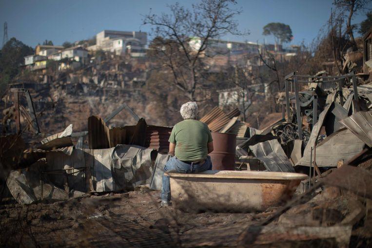 Een man kijkt naar de schade die het vuur aangericht heeft in San Roque.